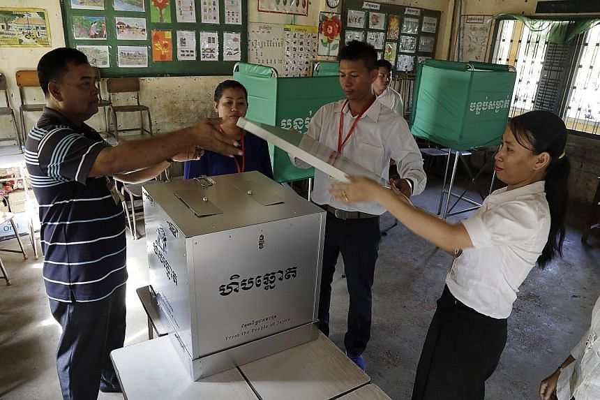 Cambodian National Election Committee officials yesterday preparing a ballot box at a polling station in Phnom Penh. Cambodia's sixth national assembly elections are being held today.