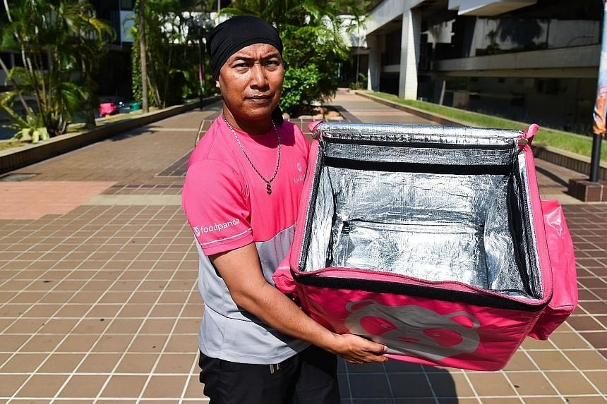 Foodpanda rider Mohamad Azli, 41, shows his delivery bag, which is cleaned and wiped down daily.