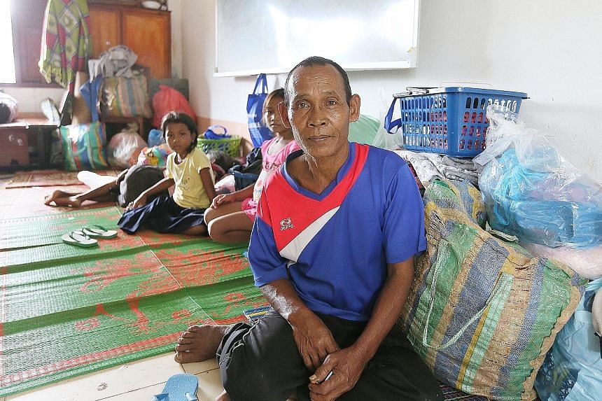 Mr Phon, 70, in a classroom at Sanamxai Secondary after his rescue. The farmer lost many of his prized possessions in the dam collapse, including his buffaloes, a small box containing the family's meagre jewellery collection, and his home.