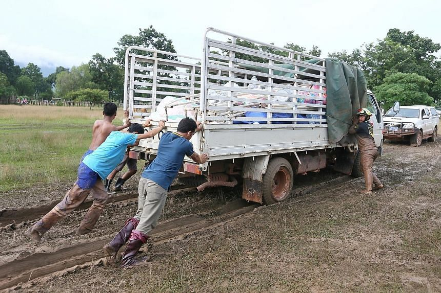 Volunteers pushing a lorry carrying supplies from the Singapore Red Cross (SRC), after it got stuck in thick mud at the Sanamxai Secondary evacuation centre yesterday. The SRC advance team will distribute items to evacuees today. Children enjoying af