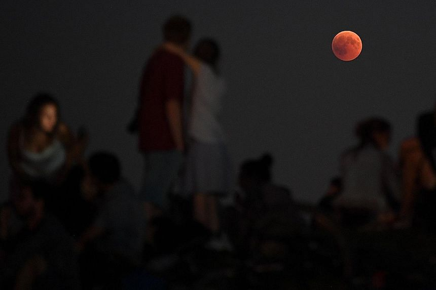 The eclipse could also be seen in (from left) Hong Kong, Munich and Athens. Lasting one hour and 43 minutes, it was the longest total lunar eclipse of the century and occurred together with the Mars opposition.