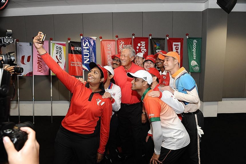 """Defence Minister Ng Eng Hen posing for a """"wefie"""" with performers preparing for yesterday's National Day Parade (NDP) preview. Dr Ng visited the F1 Pit Building and met the performers before the preview started. He wrote on Facebook after the visit: """""""