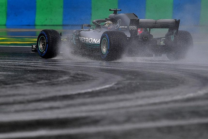 Mercedes driver Lewis Hamilton steering his car on the wet track at the Hungaroring circuit in Mogyorod near Budapest during the qualifying session yesterday.