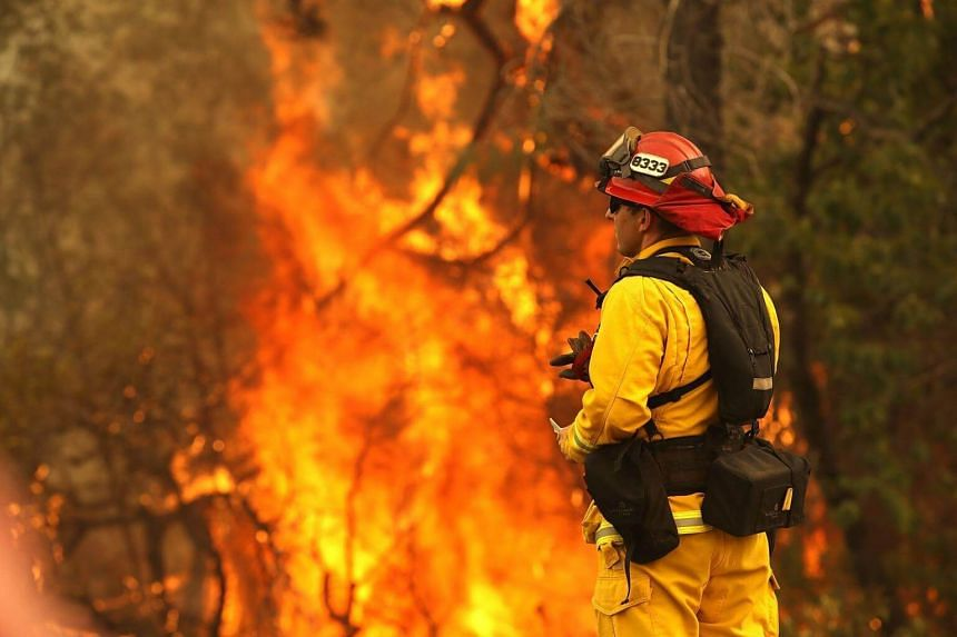 A firefighter looks on as the Carr Fire moves through an area on July 28, 2018, in Redding, California.