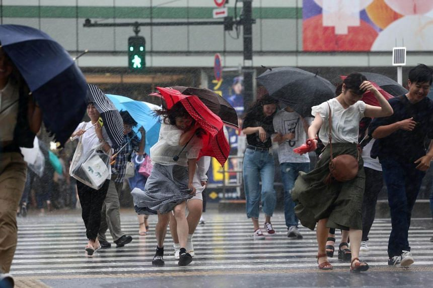 Pedestrians struggling against strong winds and rain in Tokyo, Japan, on July 28, 2018, as Typhoon Jongdari is expected to make landfall.