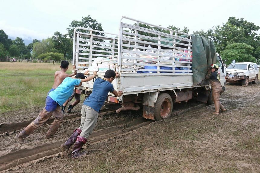 A lorry carrying Singapore Red Cross relief supplies stuck in 6 inches of mud at the Sanamxai evacuation centre, on July 28, 2018.