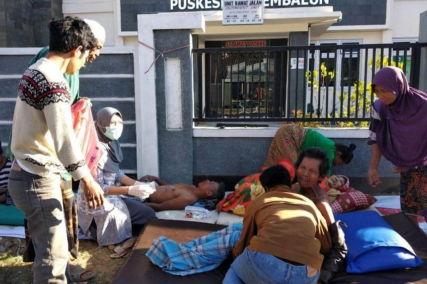 An Indonesian paramedic giving treatment to injured people outside of a hospital after an earthquake hit Sembalun Selong village in Lombok Timur, on July 29, 2018.