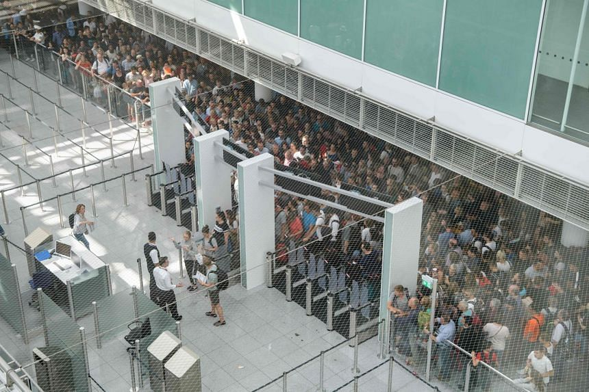 Travellers gather behinds gates at Terminal 2 at Munich airport.