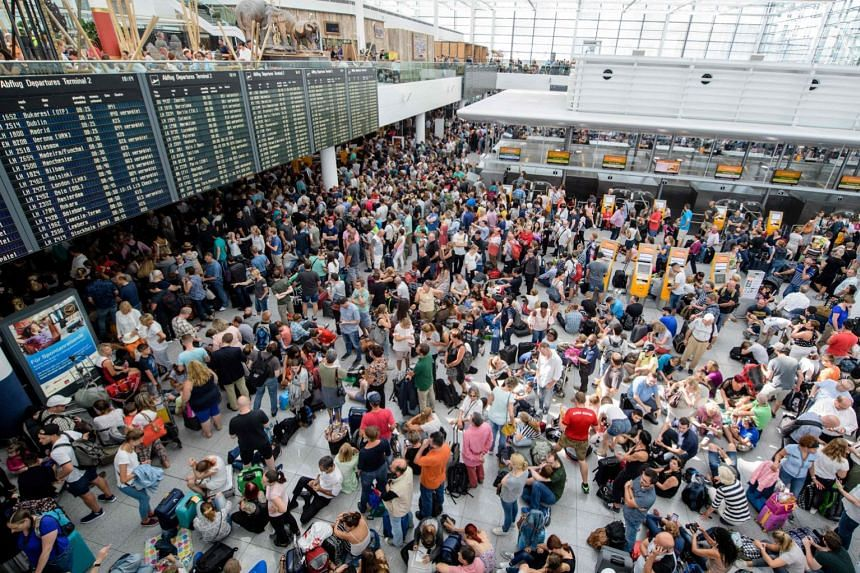 Travellers gather in front of information boards at Terminal 2 at Munich airport on July 28, 2018.