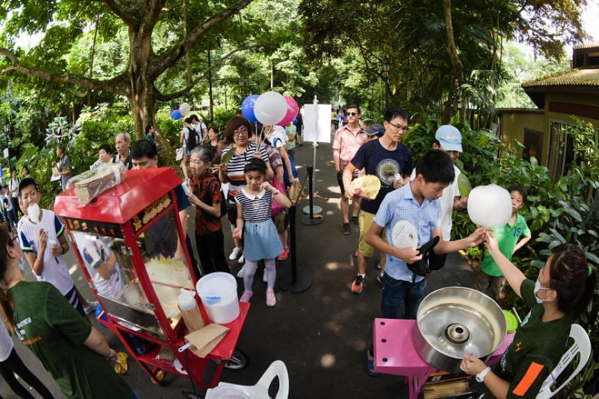 People queueing for free popcorn and cotton candy at a mini carnival organised by The Straits Times prior to the ST Concert in the Gardens in the Singapore Botanic Gardens on July 29, 2018.