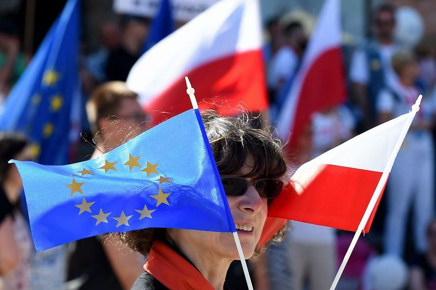 A woman holding Polish and EU flags during a protest against Poland's right-wing government.