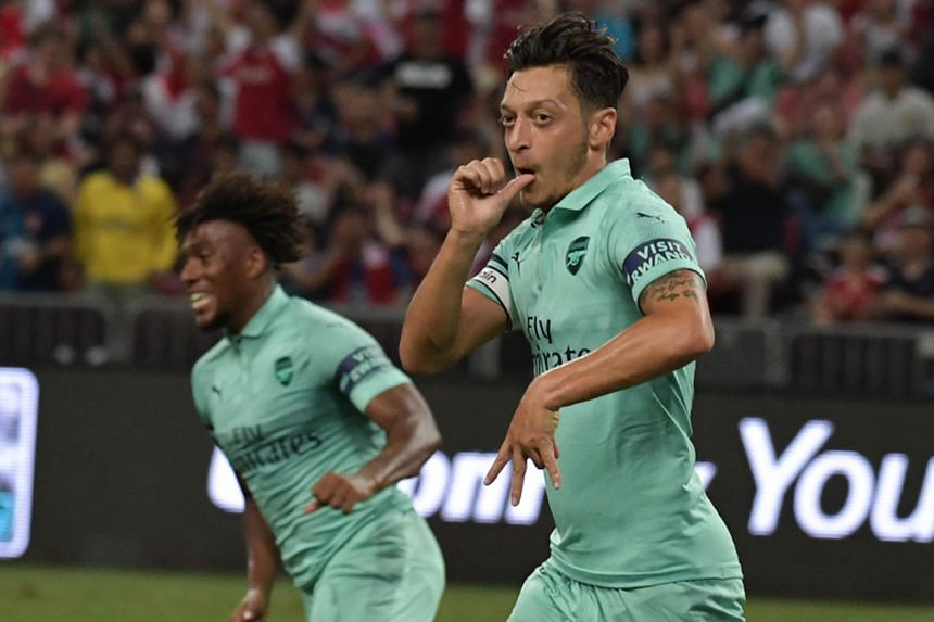 From top: PSG goalkeeper Sebastien Cibois is helpless as he watches Rob Holding's looping header sail into the net during the 5-1 ICC defeat by Arsenal at the National Stadium last night. Arsenal's captain for the night Mesut Ozil enjoying his M10 ce
