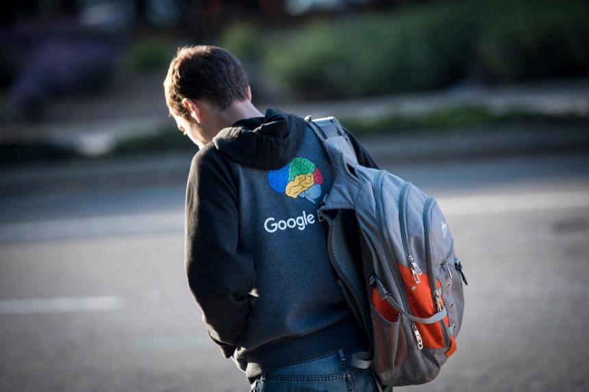A man wearing a sweatshirt with a Google logo waits for a bus in front of the company's headquarters in Mountain View, California, on April 25, 2018.