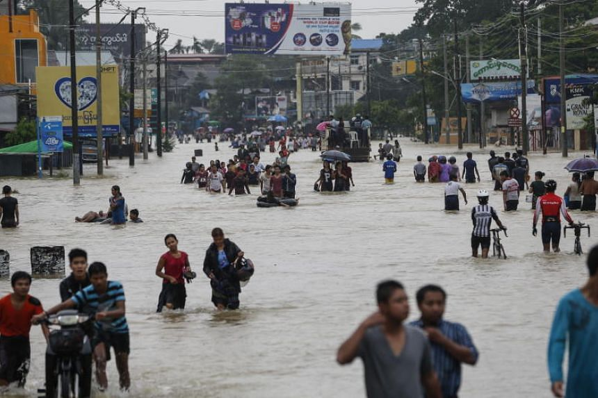 Residents wade through along a flooded Yangon-Mandalay road in Myanmay's Bago Region on July 28, 2018.