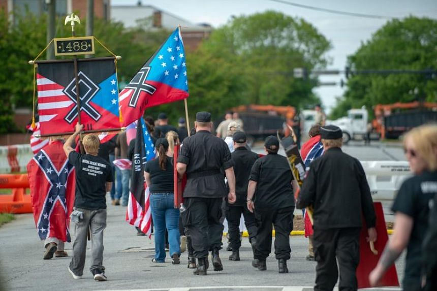A file photo taken on April 21, 2018, shows members of the National Socialist Movement and other white nationalists walk up Greenville Street in Newnan, Georgia, after a rally.