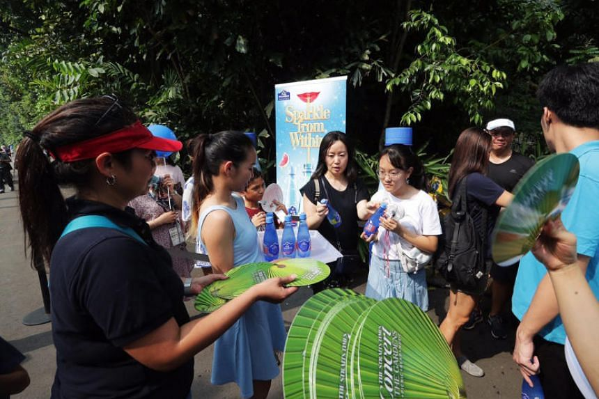 Beverages and hand-held fans being distributed to visitors at a mini carnival organised by The Straits Times prior to the ST Concert in the Gardens in the Singapore Botanic Gardens on July 29, 2018.