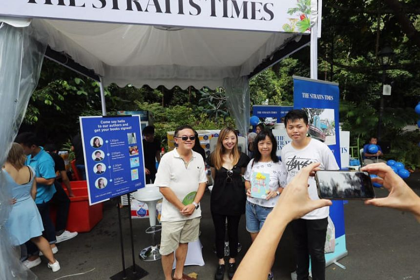 The Straits Times' executive editor Sumiko Tan (in black) poses for a photo with visitors at a mini carnival organised by the paper in the Singapore Botanic Gardens on July 29, 2018.