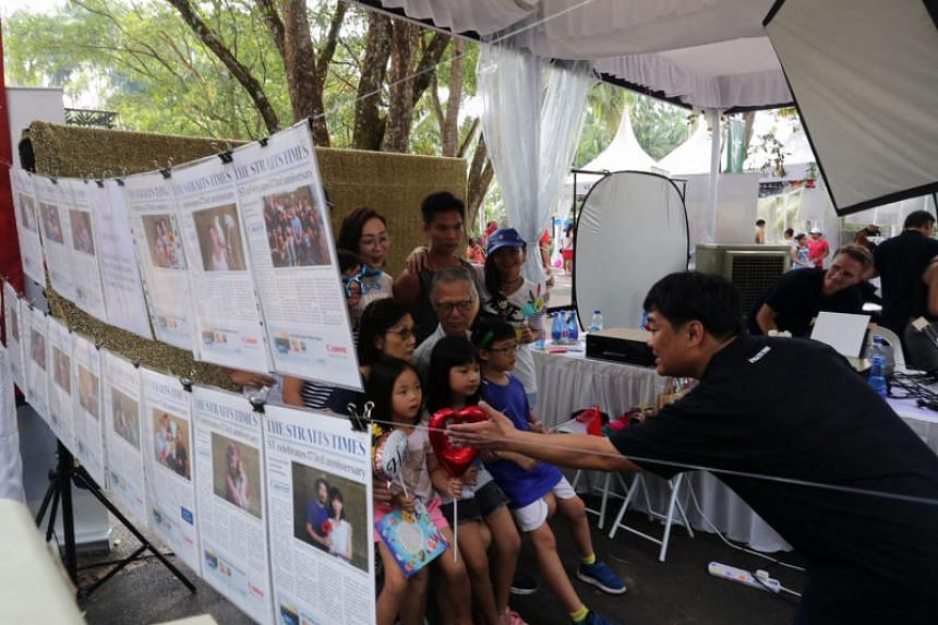 Visitors having their photos taken to be printed onto a reproduction of the front page of The Straits Times.