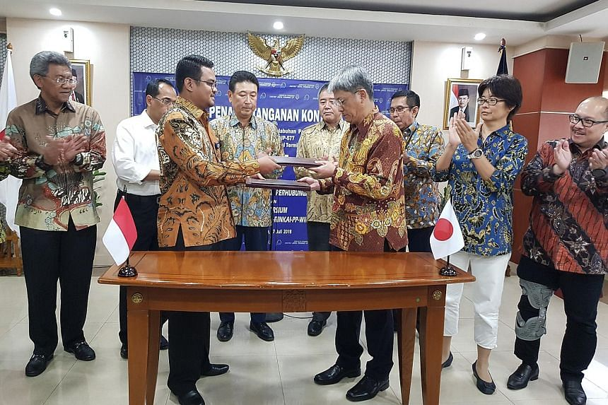 Indonesian Transportation Ministry official Aditya Karya and representative from the Indonesia-Japan consortium Hiromu Shinoda exchanging contracts of the Patimban Port project in Jakarta on Friday.