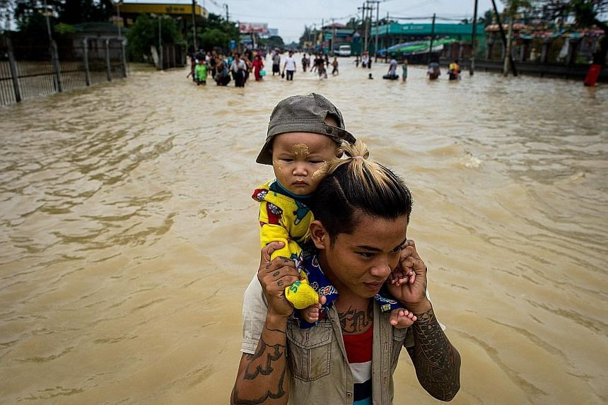 A baby being carried through flood waters in the Bago region, Myanmar, yesterday. Heavy monsoon rains have pounded the region in recent days and show no sign of abating.