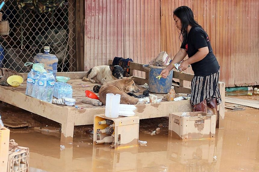 Ms Pheng outside her flood-damaged hardware store in Khokong village yesterday. Her family is safe but her store is a tangle of damaged goods. Nothing could be saved, she said.