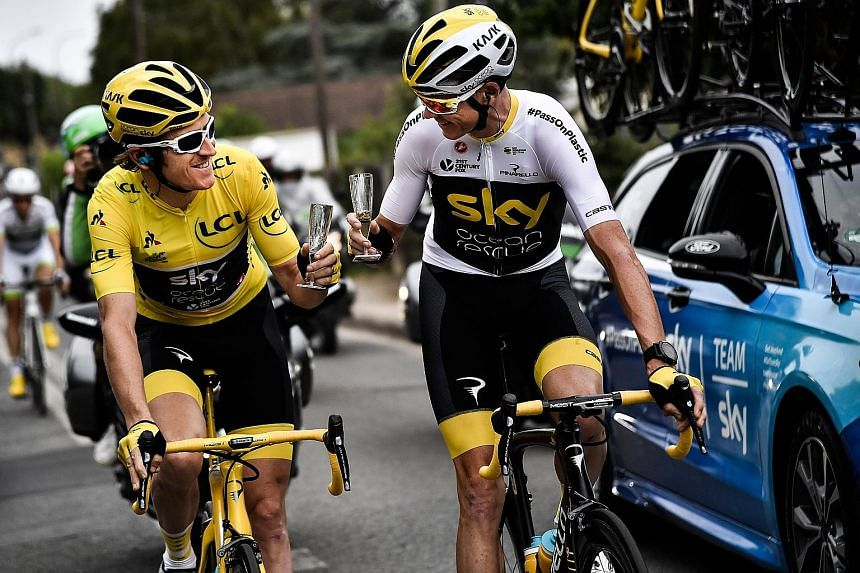 Geraint Thomas in the overall leader's yellow jersey sharing some champagne with his Sky team-mate and last year's Tour winner Chris Froome on the 21st and final stage from Houilles to Paris yesterday.