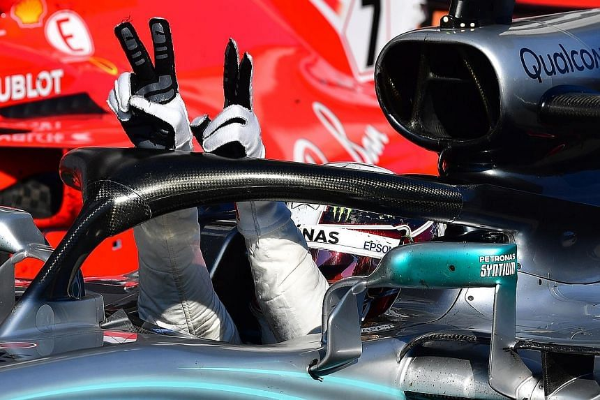 Mercedes driver Lewis Hamilton flashes the V-for-victory sign after winning the Hungarian Grand Prix yesterday. Ferrari duo Sebastian Vettel and Kimi Raikkonen were second and third respectively.