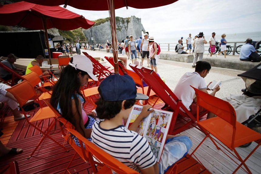 People reading books outside a library, open during the summer, in Etretat, northwestern France, on July 16, 2018.