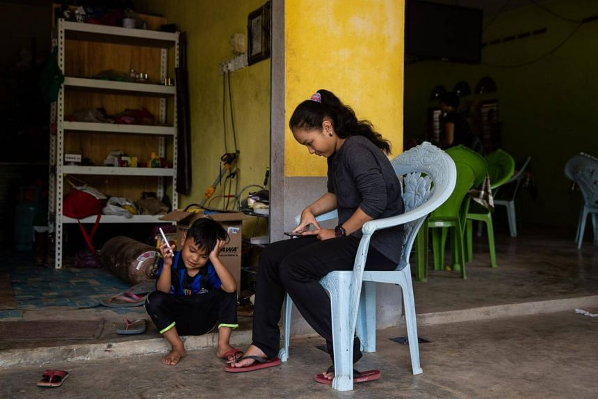Norazila, 14, at the entrance of her family's restaurant. She was dumbfounded when she found out that her friend Ayu, 11, had married her 41-year-old father.
