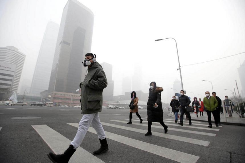A man wearing a respiratory protection mask walking towards an office building during a smog in Beijing's central business district.