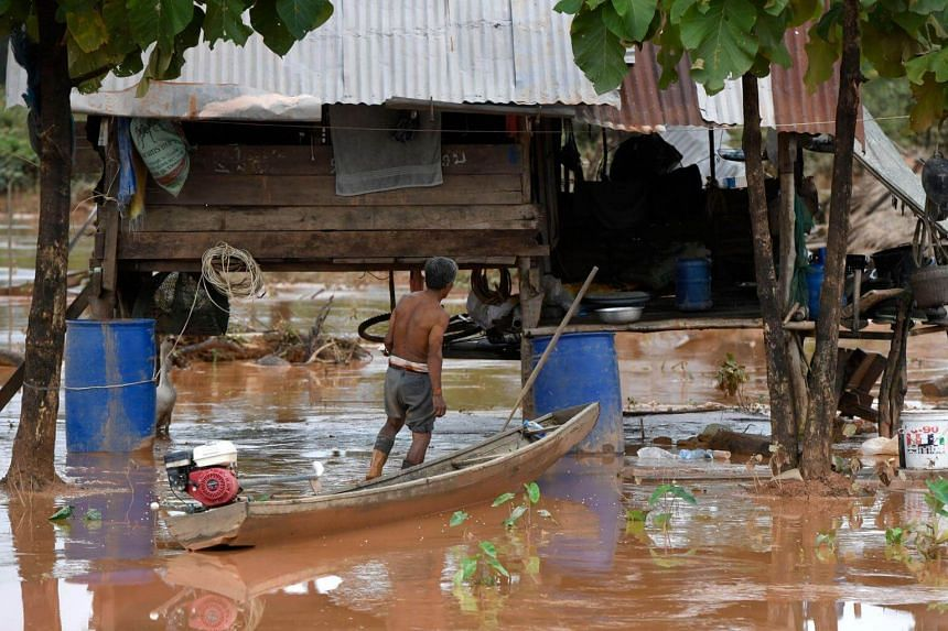 A resident returning to his home from Sanamxai district, Attapeu province, after floodwaters from a dam collapse had receded, in Laos, on July 27, 2018.