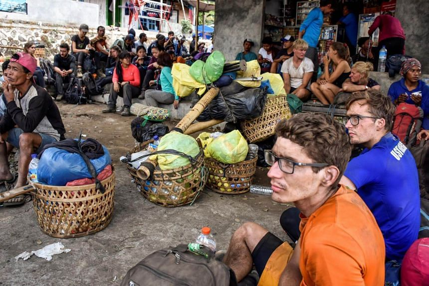Indonesian and foreign climbers after walking down from Mount Rinjani at Sembalun village in Lombok Timur, Indonesia, on July 29, 2018.