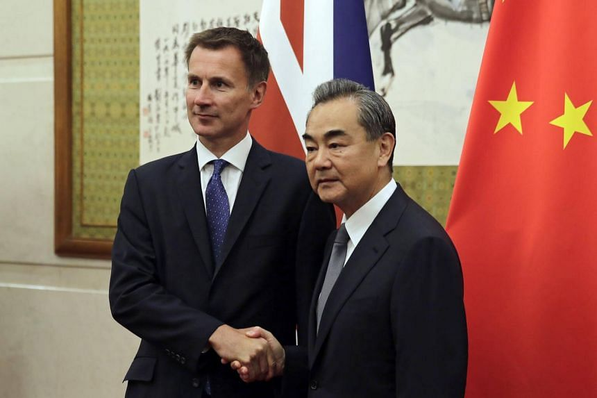 Britain's Foreign Minister Jeremy Hunt with his Chinese counterpart Wang Yi as they pose for a photograph before their meeting at the Diaoyutai State Guesthouse in Beijing, China, on July 30, 2018.