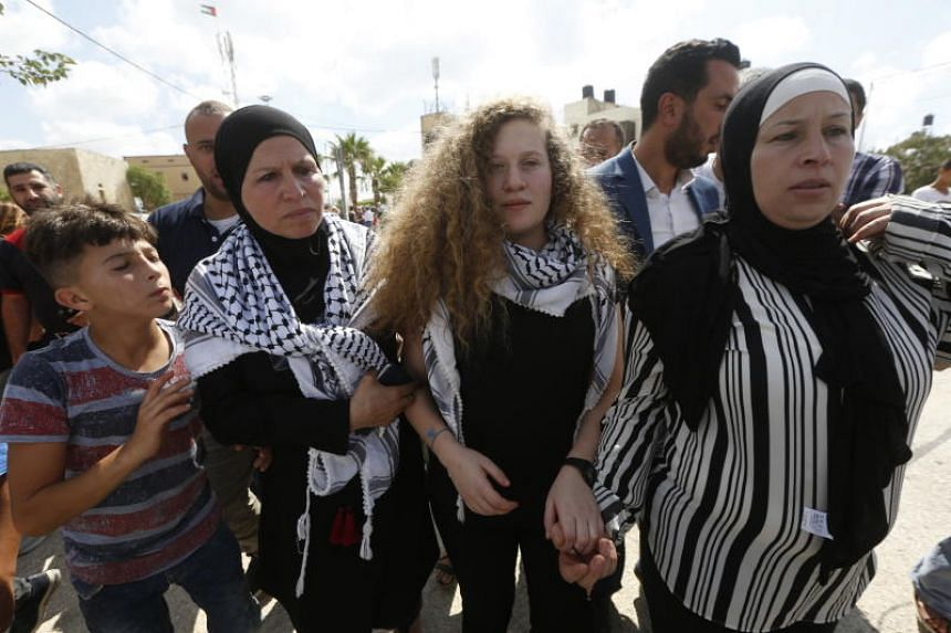 Ahed Tamimi (centre), a 17-year-old Palestinian campaigner against Israel's occupations, is welcomed with her mother Nareman (right) after she arrives at her village Nabi Salih, near the West Bank town of Ramallah, on July 29, 2018.