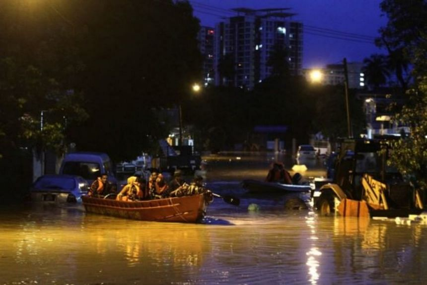 Rescue personnel evacuating some from their homes on Jalan P. Ramlee in Georgetown, Penang, following heavy rain throughout the night, on July 30, 2018.