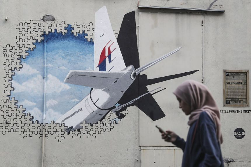 A woman walks past a MH370 mural in Shah Alam, outside Kuala Lumpur, on July 29, 2018.