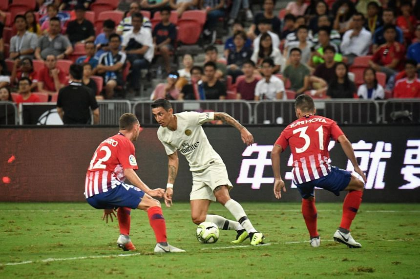 PSG's Angel di Maria taking on two Atletico Madrid players at the edge of the penalty box during the first half of the match at the National Stadium on July 30, 2018.