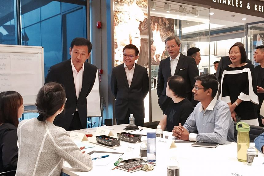 Education Minister Ong Ye Kung (third from left) speaking with Charles & Keith employees undergoing training at the company's headquarters, at the launch of a new centre to develop companies' in-house trainers.