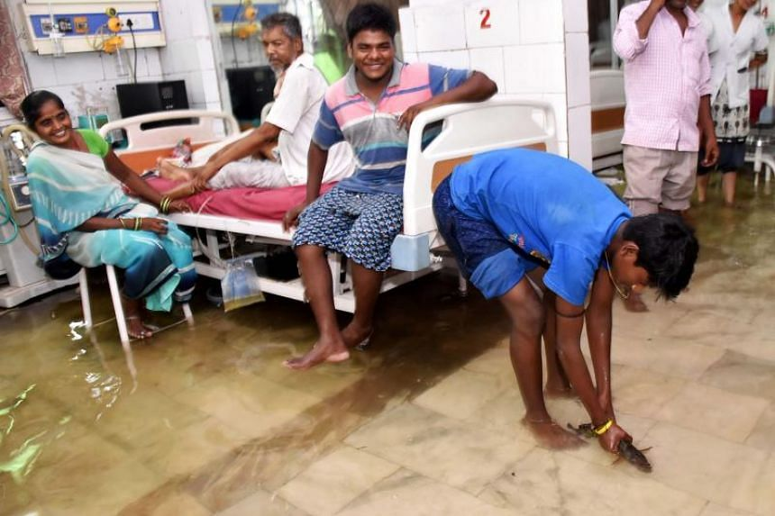 A patient's relative holds a fish inside a waterlogged hospital ward at Nalanda Medical College in Patna, India, on July 29, 2018.