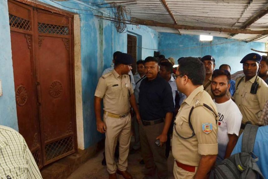 Policemen and residents stand outside the entrance of a building where seven members of a family were found hanging, in Ranchi, India, on July 30, 2018.