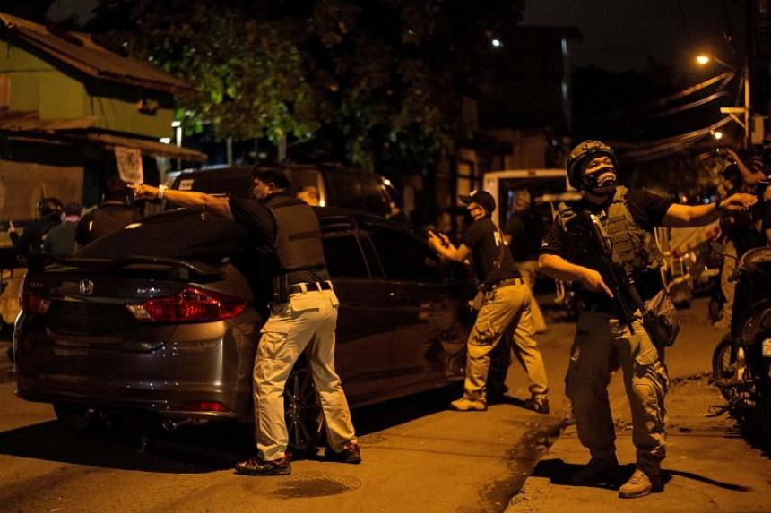 Philippine Drug Enforcement Agency agents and police secure a part of a street as they search a house during a drug raid in Taguig on Feb 28, 2018.