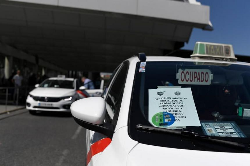 A sign on a cab announces that only minimal services will be provided amid a strike by taxi drivers outside the Atocha train station in Madrid on July 30, 2018.