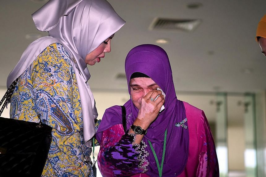 A woman who lost two family members in the MH370 incident crying after a briefing on the report.