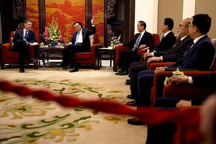 British Foreign Secretary Jeremy Hunt (left) meeting Chinese Premier Li Keqiang (raised hand) in Beijing on Monday. Foreign Minister Wang Yi (third from left) chided the US at a press conference where Mr Hunt was present.