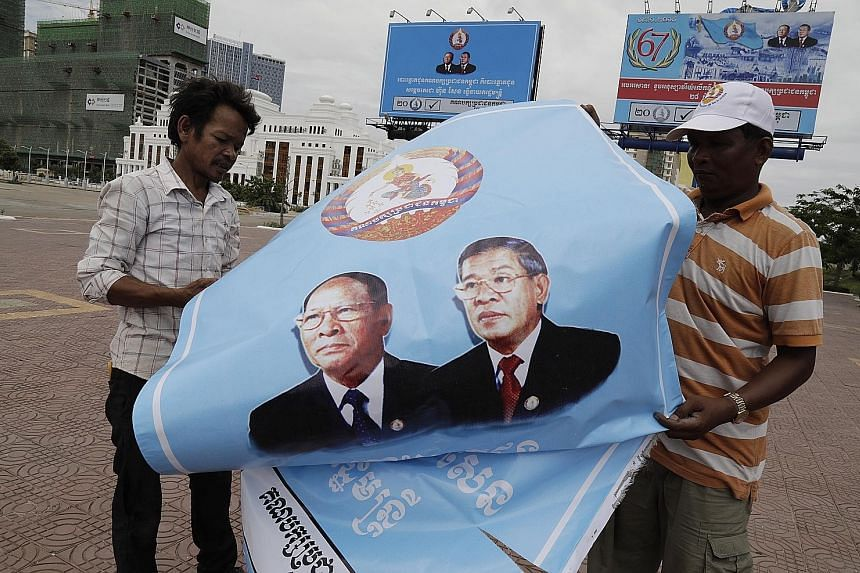 Cambodian workers folding a poster with portraits of Prime Minister Hun Sen (right) and President of the National Assembly Heng Samrin after the national elections in the country on Sunday.