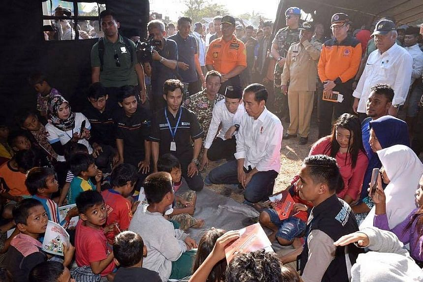 President Joko Widodo visiting victims at a makeshift shelter in Sambelia district, Lombok, yesterday. He assured them that the government will provide aid to residents whose homes were destroyed.