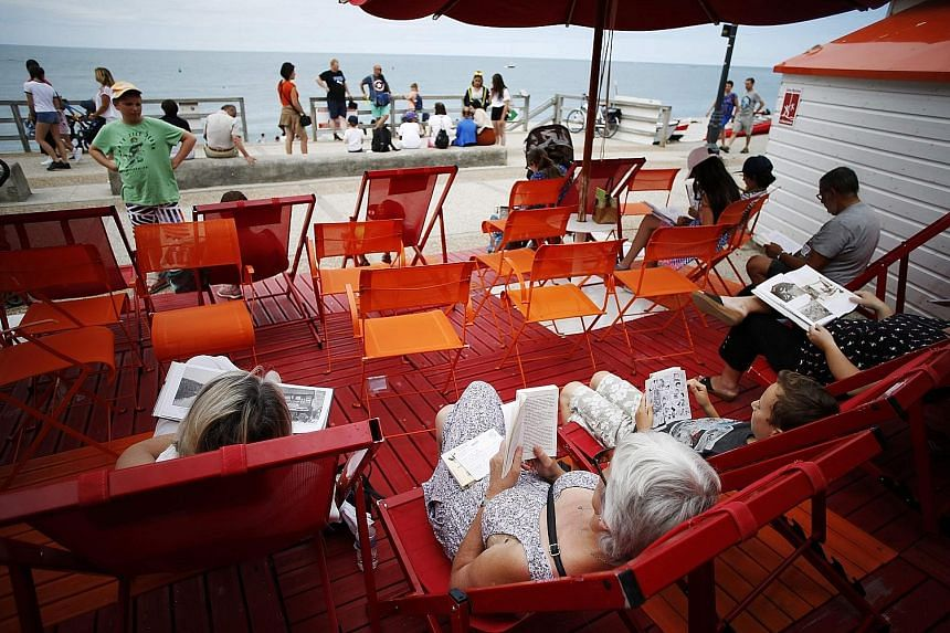 Deck chairs (above) outside a pop-up library have been set up for beachgoers who borrow books in Etretat, north-western France.