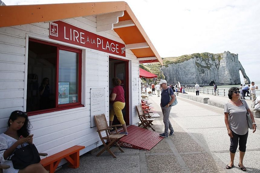 Deck chairs outside a pop-up library (above) have been set up for beachgoers who borrow books in Etretat, north-western France.
