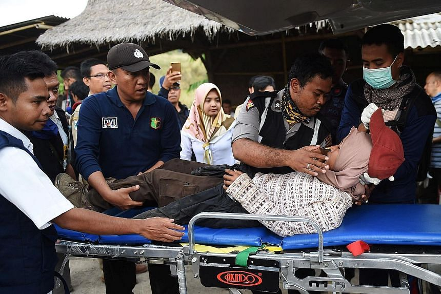 Rescue workers attending to an injured climber at Sembalun village in Lombok, Indonesia, yesterday, as their colleagues risked darkness, intermittent landslides and rockfalls to evacuate more than 560 people from Mount Rinjani following Sunday's 6.4-