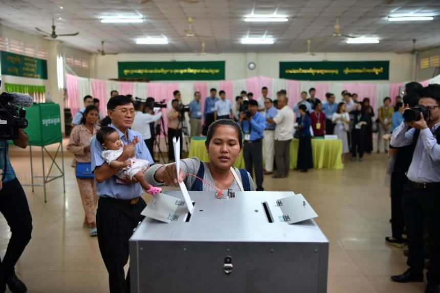 A voter drops her ballot into a box during the general election in Phnom Penh on July 29, 2018.